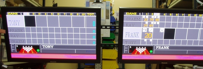 Photo - a pair of flat screen monitors with bowlers score grids